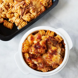 Serving Bowl of Murray's Pulled Pork Mac And Cheese Next to Container of Mac