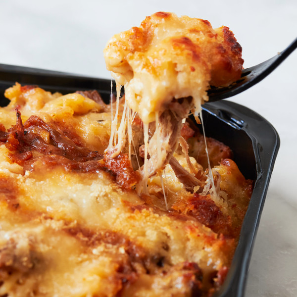 Forkful of Murray's Pulled Pork Mac And Cheese Lifted From Container of Mac