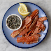 Slices of Catsmo Candy Smoked Salmon on Plate with Capers and Lemon
