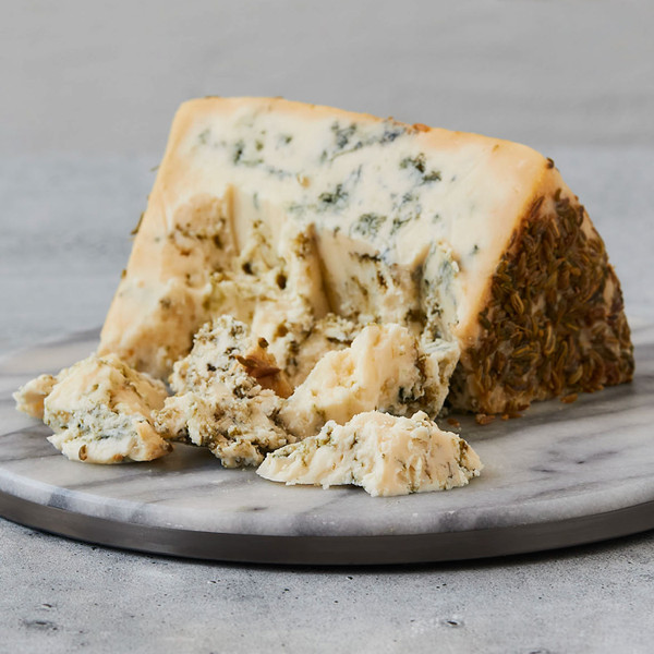 Wedge of Finocchietto Blue on a Plate with Scattered Fennel Seeds
