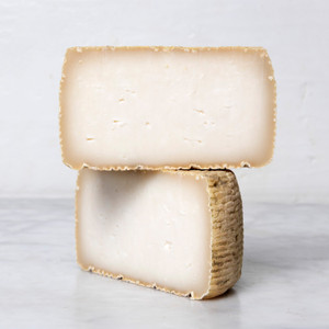 Two Half Wheels of Buttermilk Basque Stacked on Each Other