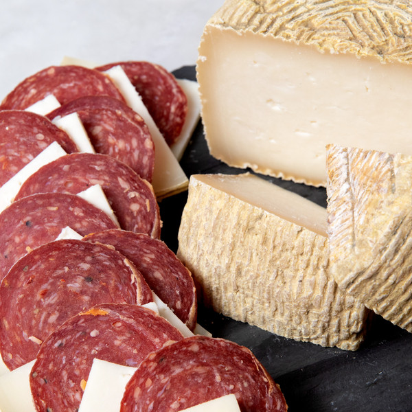 Slices of Salami Next to Wedges and a Half Wheel of Buttermilk Basque