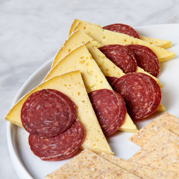 Slices of Turmeric Toma Plated with Sliced Salami and Crackers