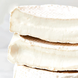 Two Halves of Robiola di Bufala Stacked on Top of a Whole Wheel of Robiola di Bufala