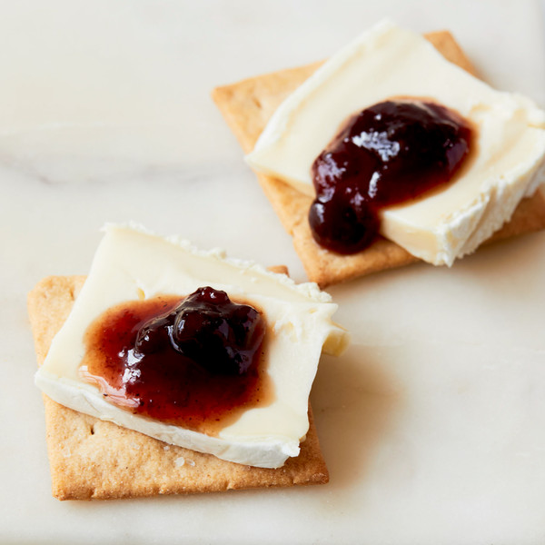 Two Moonshot Rosemary and Garlic Crackers Each Topped with Cheese and Jam