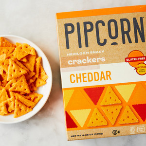 Box of Pipcorn Cheddar Crackers Next to Bowl of Loose Crackers