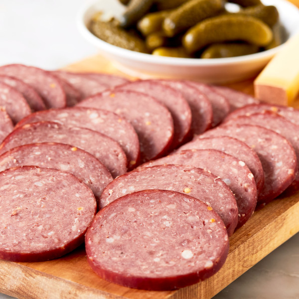 Slices of River Bear Uncured Summer Sausage on Plate with Bowl of Cornichons