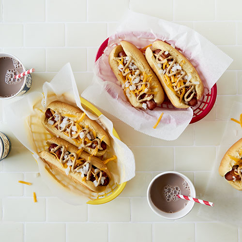 Overhead view of four Coney Island style hot dogs