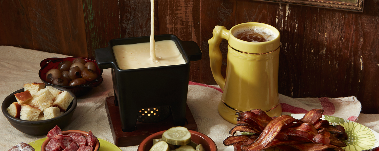 Murray's Classic Fondue in a fondue pot with bacon, pickles, salami, and bread