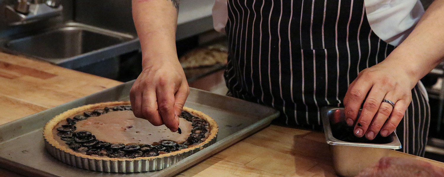 Julian Calcott placing sliced Preserved Walnuts on the Cherry Point Tart with Gjetost Caramel