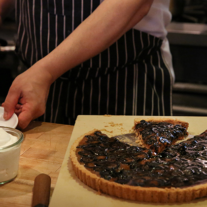 Julian Calcott cuts a slice of the Cherry Point Tart with Gjetost Caramel and Preserved Walnuts