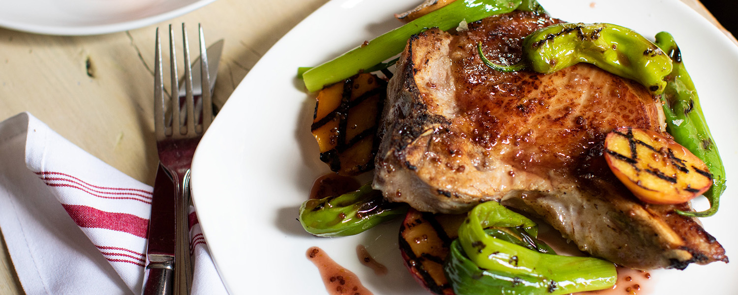 Thick cut pork chops meet grilled peaches and an a tangy-sweet sauce
